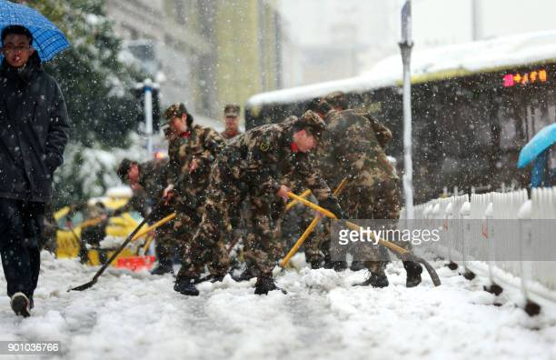 Chinese soldiers shovel snow to clear the road during a snowfall in Nanjing in China's eastern Jiangsu province on January 4 2018 An orange alert for...