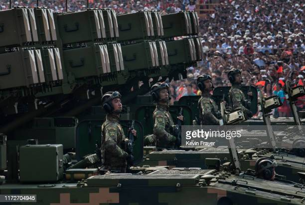 Chinese soldiers sit atop mobile rocket launchers as they drive in a parade to celebrate the 70th Anniversary of the founding of the People's...