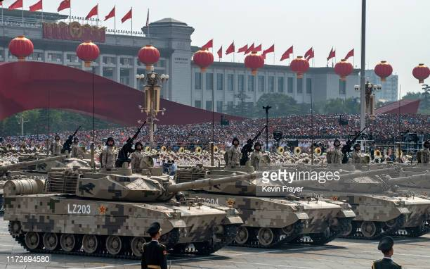 Chinese soldiers sit atop tanks as they drive in a parade to celebrate the 70th Anniversary of the founding of the People's Republic of China in...