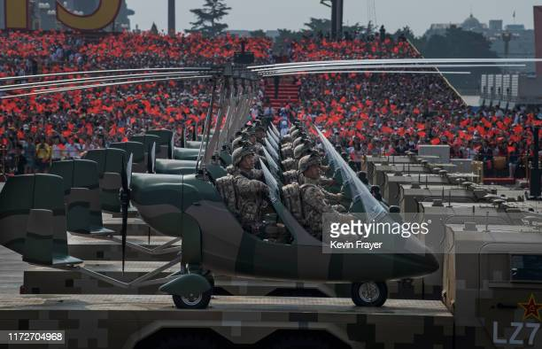 Chinese soldiers sit in small helicopters as they ride on trucks in a parade to celebrate the 70th Anniversary of the founding of the People's...