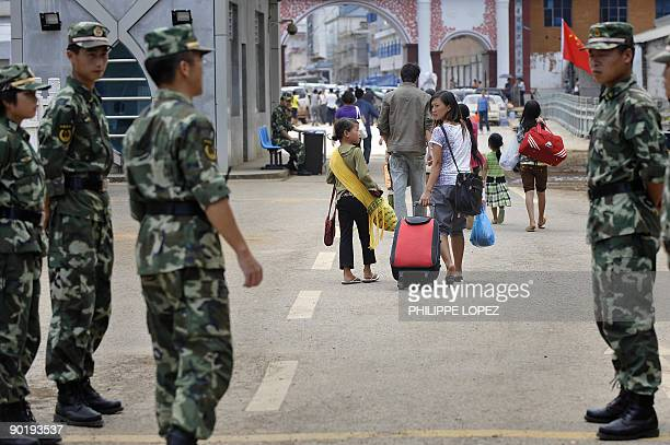 Chinese soldiers stand guard as refugees cross the border towards Myanmar in the Chinese border town of Nansan on August 31 2009 around 700 kms from...