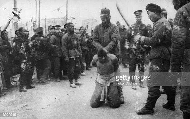 Chinese soldiers stand round as a prisoner is made ready for execution during the 1912 Revolution in China