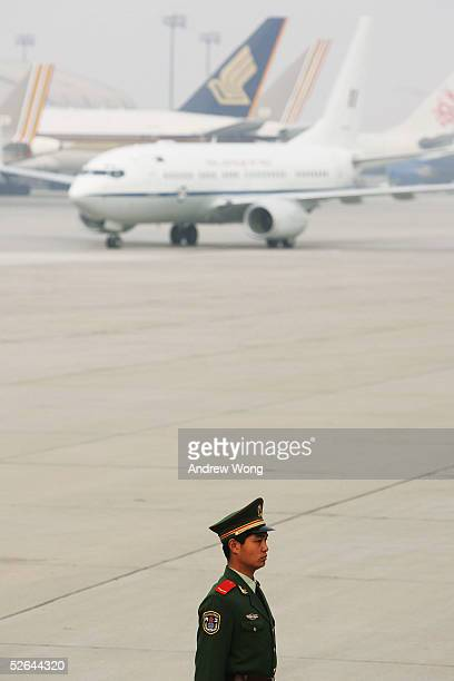 Chinese soldlier stands guard as the plane carrying Australian Prime Minister John Howard and his wife Janette arrives at the Capital International...
