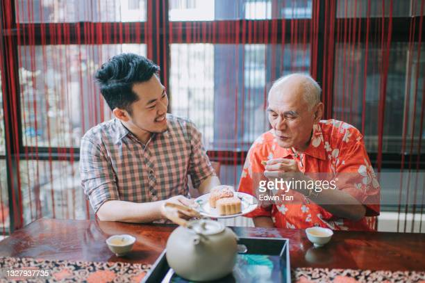 chinese son sharing mooncake to his father during traditional mid-autumn festival at home during afternoon tea gathering - moon cake stock pictures, royalty-free photos & images