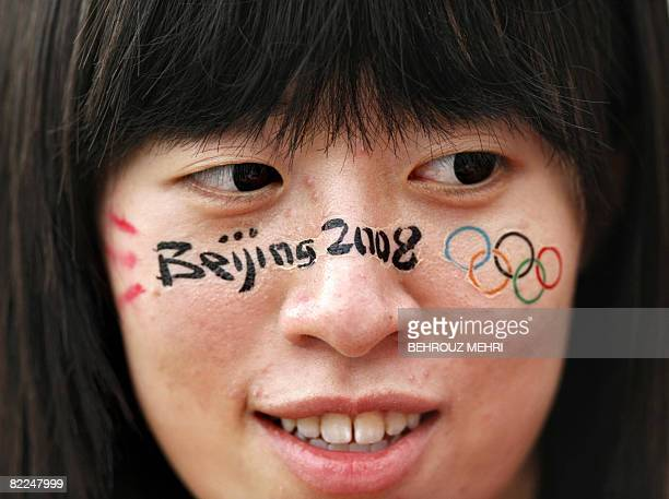 Chinese spectator has a sticjer featuring the Olympic rings on her face as she watches a tennis match of the 2008 Beijing Olympic Games at the...