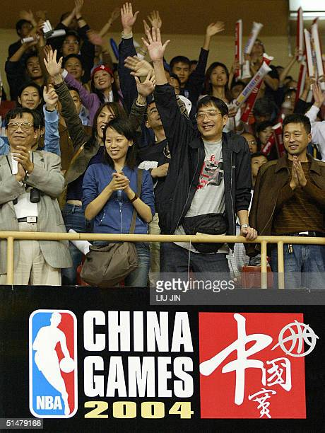 Chinese spectators cheer during the NBA presession match between Houston Rockets and Sacramento Kings at Shanghai Stadium 14 October 2004 Houston...