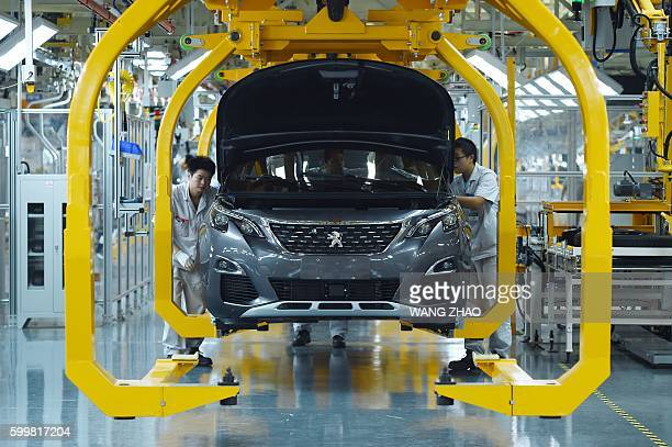 Chinese staff work on the assembly line at the start of production on the DPCA Chengdu plant and Dongfeng Peugeot 4008 line in Chengdu on September 7...