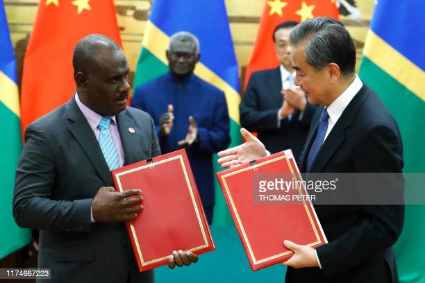 Chinese State Councillor and Foreign Minister Wang Yi and Solomon Islands Foreign Minister Jeremiah Manele attend a signing ceremony at the Great...
