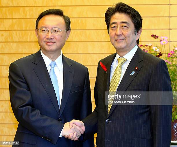 Chinese state councilor Yang Jiechi and Japanese Prime Minister Shinzo Abe shake hands during their meeting at Abe's official residence on October 14...