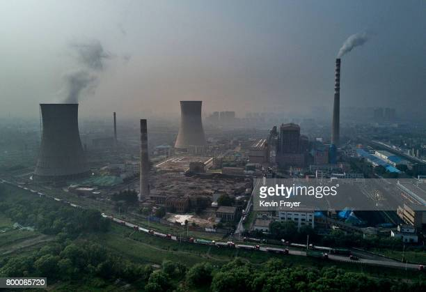 Chinese state owned coal fired power plant is seen near a large floating solar farm project under construction by the Sungrow Power Supply Company on...