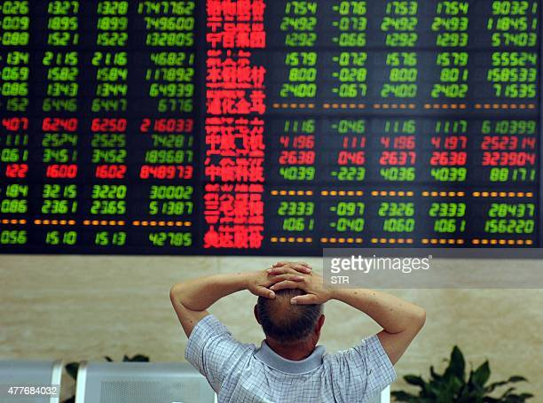 A Chinese stock investor monitors share prices at a securities firm in Fuyang in China's Anhui province on June 19 2015 Shanghai shares plunged 642...