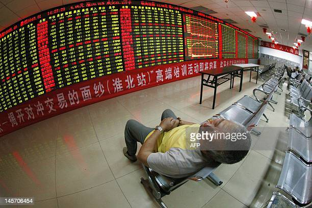Chinese stock investor naps as he monitors his share prices at a stock brokerage firm in Huaibei, east China's Anhui province on June 4, 2012....