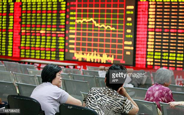 Chinese stock investors monitor their share prices at a stock brokerage firm in Huaibei, east China's Anhui province on June 4, 2012. Chinese...