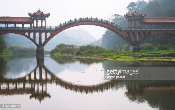 chinese stone arch bridge over the min jiang river in leshan , sichuan province , china . - ponte ad arco foto e immagini stock