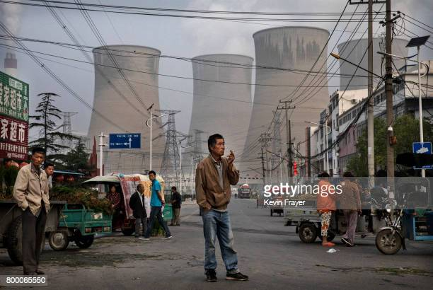 Chinese street vendors and customers gather at a local market outside a state owned Coal fired power plant near the site of a large floating solar...