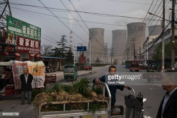 Chinese street vendors wait for customers at a local market outside a state owned coal fired power plant near the site of a large floating solar farm...