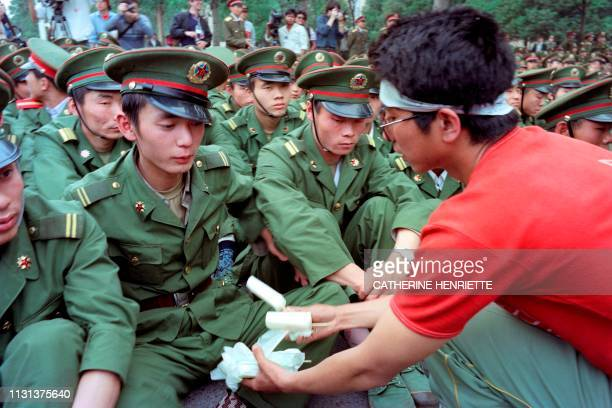 Chinese striking student offers ice creams to Peole's Army of Liberation soldiers seated in front of the Great Hall of the People where President...