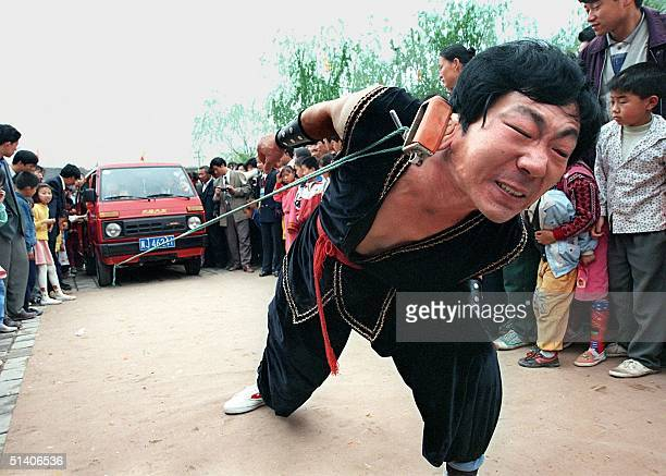 Chinese strongman Li Jianhua pulls a van loaded with eight children with a rope clipped to one of his ears during a performance in the northeastern...