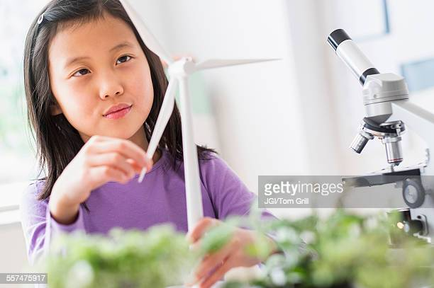 Chinese student examining model wind turbine in science lab