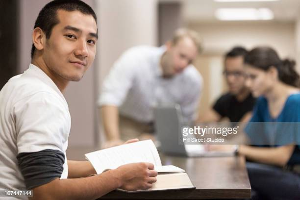 Chinese student reading book at desk
