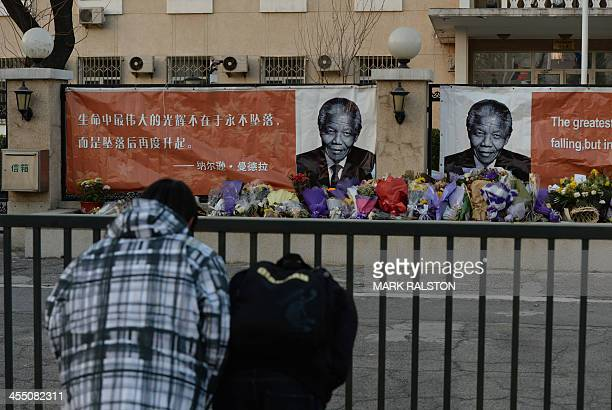 Chinese students bow before portraits at a memorial to the late South African leader Nelson Mandela outside the South African embassy in Beijing on...