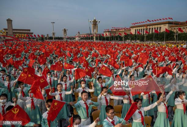 Chinese students from a choir wave party and national flags at a ceremony marking the 100th anniversary of the founding of the Communist Party on...