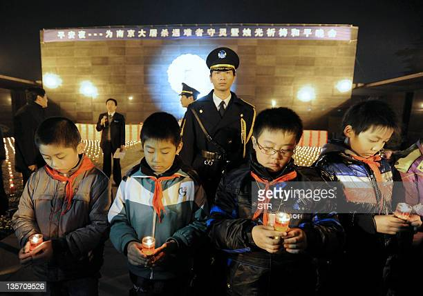 Chinese students holding candles mourn for victims at a ceremony at the Nanjing Massacre memorial monument in Nanjing eastern China's Jiangsu...