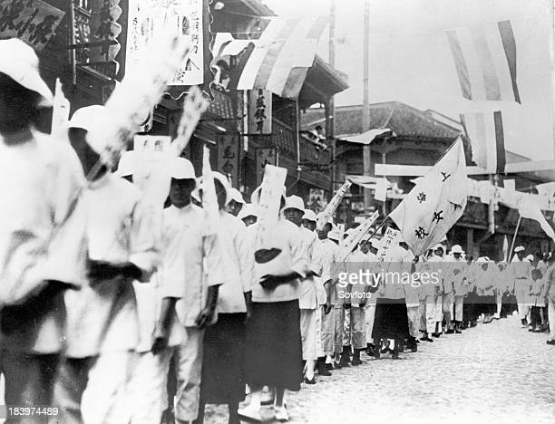 Chinese students of all ages marching with banners reading 'Down with the traitors who buy Japanese goods' during demonstrations in Shanghai in 1919