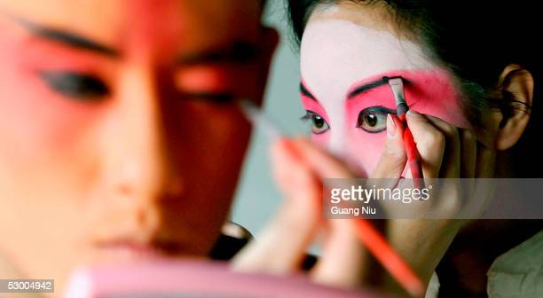 Chinese students paint their faces in preparation for a performance of the Peking Opera during the annual celebration for the International...