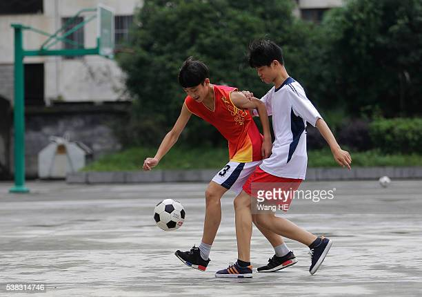 Chinese students play football at the campus of the Yuyang Middle School in Wufeng Tujia Nationality Autonomous County of Yichang on June 3 in Hubei...