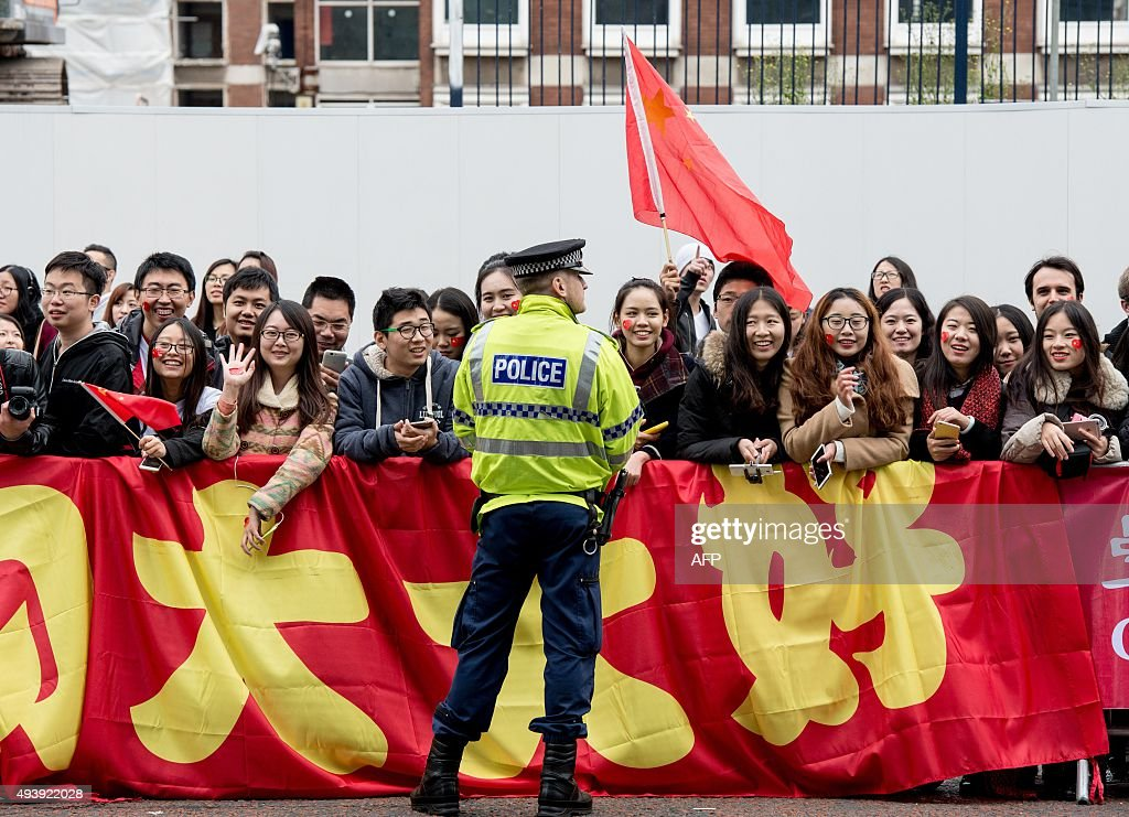 Chinese students show support for Chinese President Xi Jinping as he arrives to tour the National Graphene Institute at Manchester University with Britain's Chancellor of the Exchequer George Osborne on October 23, 2015 in Manchester, north west England. Chinese President Xi Jinping blew the final whistle on his state visit to Britain today with a day out at the English Premier League leaders Manchester City. AFP PHOTO / POOL / Richard Stonehouse