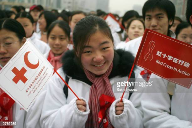 Chinese students wave flags during an Aids awareness event as China marks World Aids Day November 29 2003 in Beijing China United Nations Secretary...