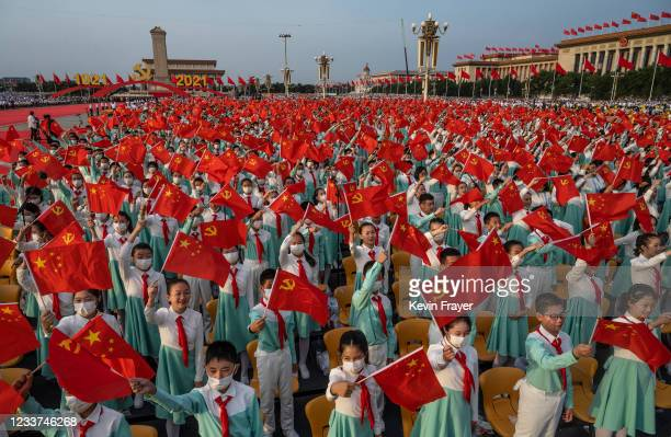 Chinese students wave party and national flags at a ceremony marking the 100th anniversary of the Communist Party at Tiananmen Square on July 1, 2021...
