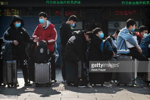Chinese students wear masks as they wait to take a train after the Spring Festival holiday on January 31 2020 in Beijing China The number of cases of...
