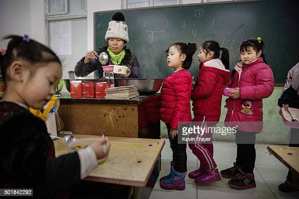 Chinese students who are children of migrants wait in line for lunch in a classroom at an unofficial school on December 18 2015 in Beijing China...