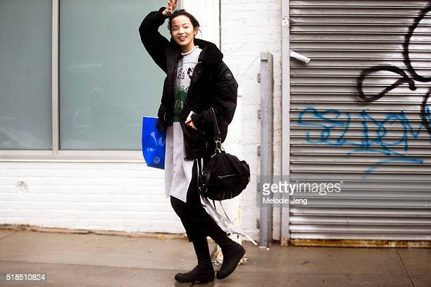 Chinese supermodel Xiao Wen Ju wears a black Canada Goose coat and a gray cotton dress with a fringe after the Rodarte show during New York Fashion...
