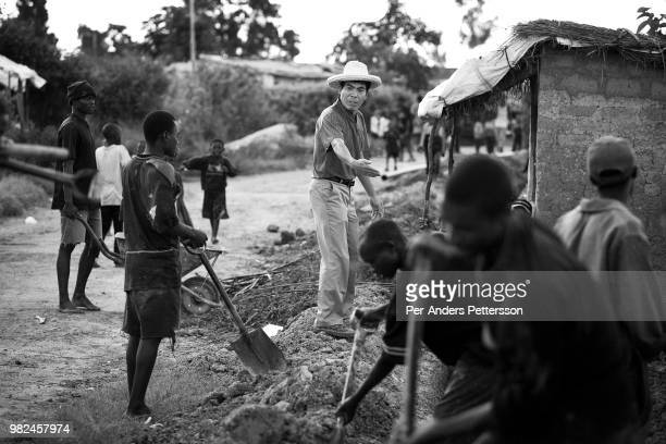Chinese supervisor gives instructions to Zambian workers who dig trenches for water pipes on March 23 2007 in Kabwe Zambia He works for China GEO...