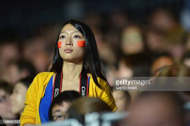 A Chinese supporter cheers her team during the table tennis men's team final China vs South Korea at the London Olympic games on August 8 2012 at the...