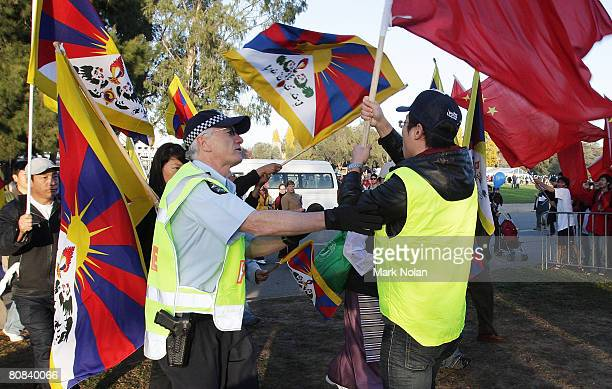 Chinese supporter confronts anti Chinese people with a flag and is stopped by a policeman before the start of the Olympic Torch relay at...