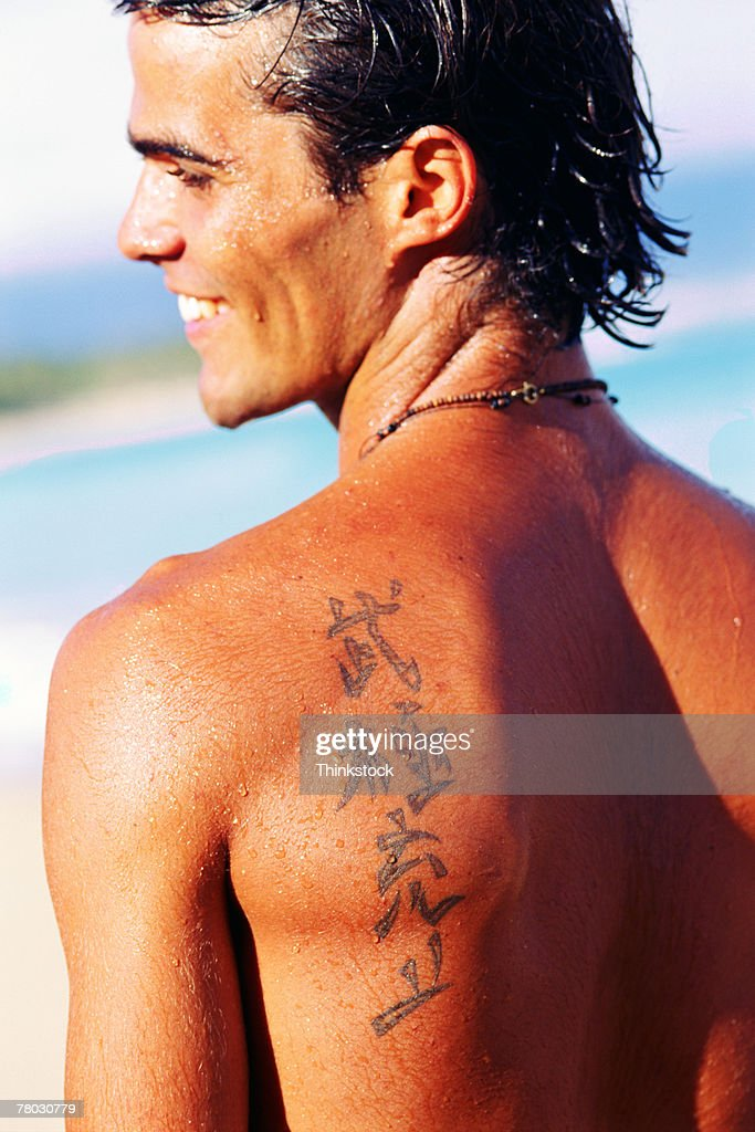 Chinese symbols tattooed on man's shoulder : Stock Photo