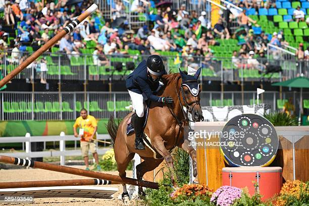 Chinese Taipei's Isheau Wong on Zadarijke V crashes through an obstacle during the Equestrian's Show Jumping first qualifier event of the 2016 Rio...