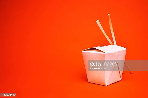 Chinese takeout container with chopsticks, isolated on red