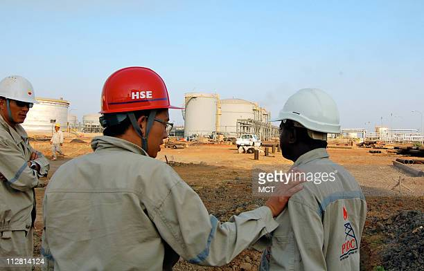 Chinese talks to a co-worker at an oil production facility in Southern Sudan's Melut County. China has strengthened its relations with Southern Sudan...