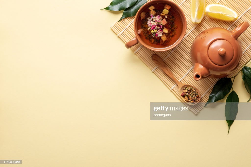 Chinese tea ceremony. Ceramic teapot, teacup, green leaves, wooden spoon with dried tea on bamboo mat on yellow background. Top view : Stock Photo
