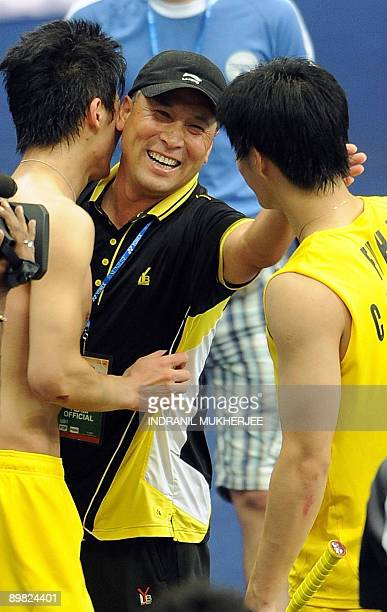 Chinese team head coach Li Yung Bao greets Fu Haifeng and Cai Yun of China after their win aginst Jung Jae Sung and Lee Yong Dae of South Korea in...