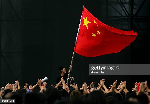 Chinese teenager waves a national flag during a rockandroll festival to mark Chinese National Day on October 2 2005 in Beijing China Various...