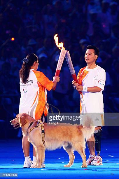 Chinese torchbearer Sun Changting and Ping Yali pass on the Paralympic flame during the Opening Ceremony for the 2008 Paralympic Games at the...