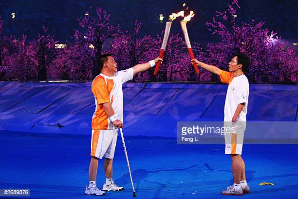 Chinese torchbearer Wu Yunhua and Zhao Hongwei pass on the Paralympic flame during the Opening Ceremony for the 2008 Paralympic Games at the National...