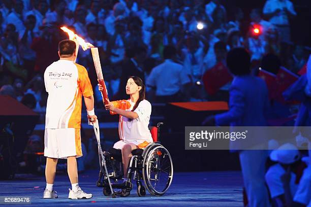 Chinese torchbearers Jin Jing and Wu Yunhua and Zhao Hongwei pass on the Paralympic flame during the Opening Ceremony for the 2008 Paralympic Games...