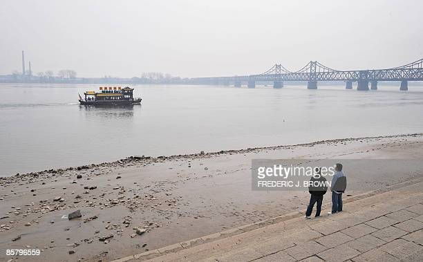 A Chinese tour boat approaches the SinoKorean Friendship bridge over the Yalu River on April 4 in Dandong in northeast China's Liaoning province as...